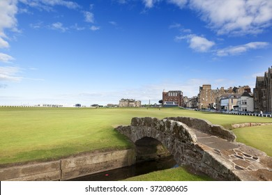 ST ANDREWS-SEPTEMBER14, 2013: The famous Swilken Bridge on the Royal and Ancient Golf course, St Andrews Scotland with Clubhouse and Hamilton Hall in background on september 14, 2013