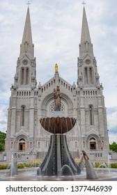 St Anne de Beaupre, Quebec, Canada - June 24, 2010: The front of the Basilica of Sainte-Anne-de-Beaupré church with statue of Saint Anne by Canadian sculptor Émile Brunet on a fountain.