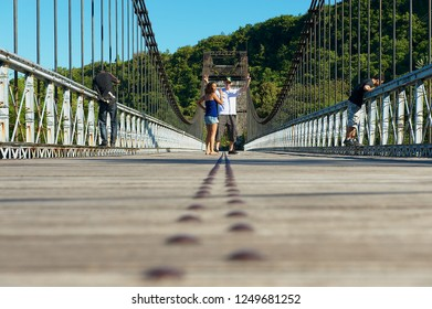 St. Anne, Reunion - December 06, 2010: Unidentified tourists walk by the old suspension Bridge Pont Des Anglais in St. Anne, Reunion.