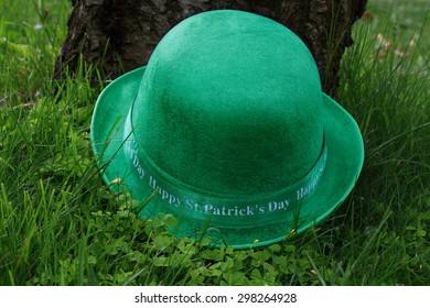 St. Patrick?s Arrangement - green men hat (derby hat), over clover (shamrocks) and grass in front of cherry tree