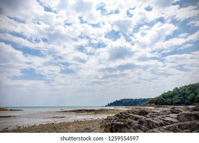St Aubin in Jersey. The tide is out leaving a wet beach and a yacht just offshore..  There are rocks in the foreground and a wooded headland jutting out into the sea.  A cloud filled sky is above.
