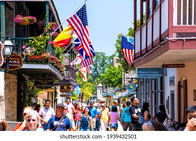 St. Augustine, USA - May 10, 2018: People shopping at Florida city St George Street by stores shops and restaurants in old town city with American and international flags