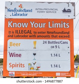 St. Barbe, Newfoundland - 6/15/2019: Weathered sign posted at Newfoundland - Labrador ferry terminal illustrating the maximum amount of alcohol allowed to be transported into Newfoundland and Labrador