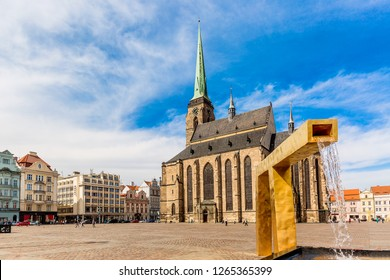 St. Bartholomew's Cathedral in the main square of Plzen with a fountain on the foreground against blue sky and clouds sunny day. Czech Republic, Pilsen. Famous landmark in Czech Republic, Bohemia.
