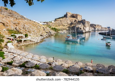 St. Paul´s bay with boats, Lindos acropolis in background (Rhodes, Greece)
