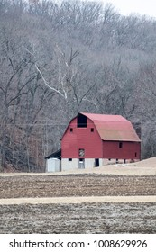 St. Charles County, MO/United States - January 20, 2018: Red barn sits between barren farm land and wooded trees as farmers wait for spring.