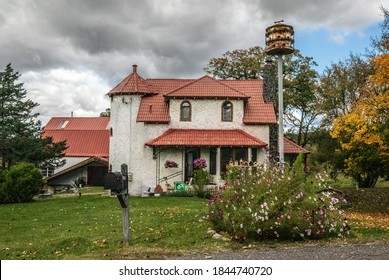 St. Croix Falls, WI USA September 30, 2020 Beautiful Spanish style stucco home with a tower and a roof made from tiles. Birdhouses and cosmos growing ina garden out front.
