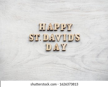 St. David's Day greeting card. Isolated background, close-up, view from above, wooden surface. Congratulations for relatives, friends and colleagues