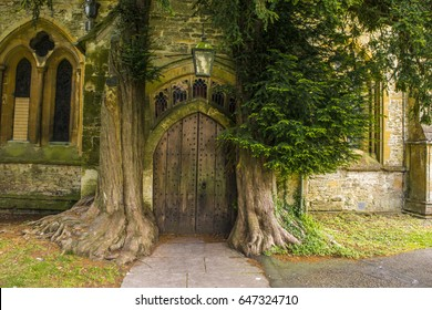 St Edward - Parish Church north door flanked by yew trees - Cotswolds - England