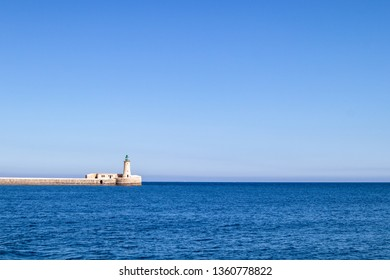St. Elmo Lighthouse at grand harbor in Valletta Malta. Bright blue sea and sky. Historic sight to see.