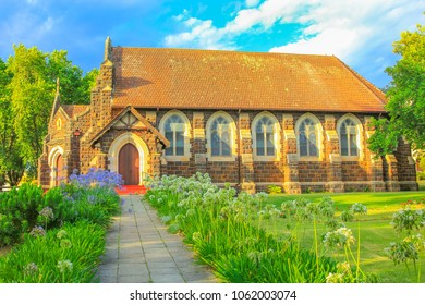 St. Georges Anglican Church and flowered garden in Knysna, city on the Garden Route in Western Cape, South Africa. The historic Church as built in 1855. Sunset shot. Side view.