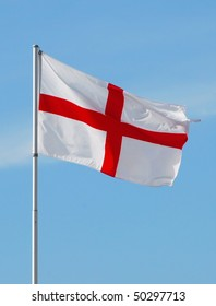 """St George's cross flag flying on a sunny day. This is a red cross on a white background. The design has been in use since the crusades, and it became associated with Saint George, the """"warrior saint"""""""