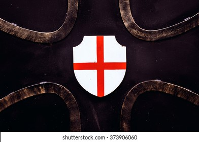 St George's Cross on a shield attached to an old metal gate.