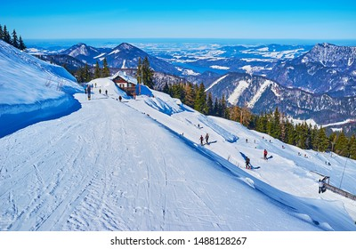 ST GILGEN, AUSTRIA - FEBRUARY 23, 2019: The skiers on the slope of Zwolferhorn mount, observing Alpine peaks and Fuschlsee lake, those are seen on the distance, on February 23 in St Gilgen