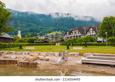 St. Gilgen, Austria - June 2, 2017: Beach on Wolfgangsee lake with woodens seats, children's playground, green lawn and a view of mountains. Cloudy summer day in alpine town on Wolfgangsee lake.