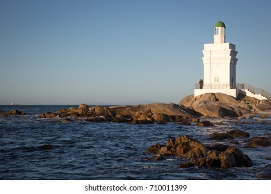 St Helena  Bay, Cape Town, South Africa - August 26, 2017: White Light House on the beach with ocean and rocks in the foreground in St Helena Bay West Coast Cape Town South Africa