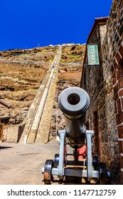 ST HELENA ISLAND, SOUTH ATLANTIC - APRIL 2 2018: Showing scale of the steep climb of 699 steps of Jacobs Ladder in Jamestown Saint Helena with old cannon in foreground