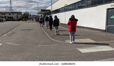 St Helens, Merseyside. UK 03/29/2020 Line of customers queuing to get into a supermarket to buy essentials  keeping 2 meters apart as per government social distancing advice during the COVID19 virus.