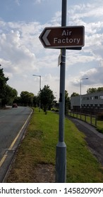 ST Helens, Merseyside UK 07/15/2019 A brown tourist information sign with the words Air Factory in white text attached to a lamp post pointing to the left of frame against a lightly cloudy blue sky.