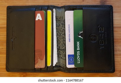 St Helens, UK August 26 2018 Males leather wallet showing a UK photo card drivers license and a Lloyds bank card.