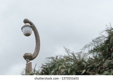 St Ives, Cambridgeshire, UK - Circa April 2019: Isolated view of a 1970s, pressed concrete street light. Showing signs of decay, it can be seen near an adjacent hedge at the end of a street.