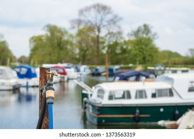 St Ives, Cambridgeshire, UK - Circa April 2019:  Isolated view of a water tap and house seen at a boat yard at an inland waterway. Used to replenish coolant for boat engines.