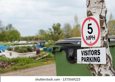 ST Ives, Cambridgeshire, UK - Circa April 2019: Close-up if a 5mph speed limit seen seen at the entrance to a boat yard and marina. Boats can be seen moored across the road, into the distance.