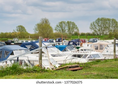 St Ives, Cambridgeshire, UK - Circa April 2019: Dozens of moored cabin cruisers and boats seen within a marina at an inland waterway. Both private owners and hired vessels are harboured here.