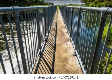 St Ives, Cambridgeshire, UK - Circa May 2019: High contrast, shallow focus of a narrow footbridge seen crossing a large weir in the English countryside in early summer.