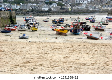 St Ives Cornwall circa May 2015. Two dozen small and medium sized boats moored haphazardly on sandy beach with town houses in background. Tide is out.
