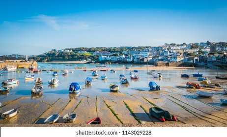 St. Ives, Cornwall / UK - 08 28 2017: Fishing boats during low tide in the evening at sunset at the harbor of St Ives vacation, fishing town in Cornwall, United Kingdom, UK.