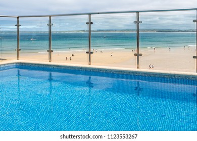ST IVES, ENGLAND - JUNE 18: View from a clear, blue swimming pool, over Porthminster Beach. In St Ives, Cornwall, England. On 18th June 2018.
