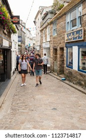 ST IVES, ENGLAND - JUNE 18: Tourists exploring the back streets in St Ives, Cornwall, England. Fore Street, in St Ives, Cornwall, England. On 18th June 2018.