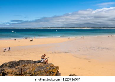 ST IVES, ENGLAND - JUNE 18: Man playing guitar on Porthminster Beach, St Ives, on a hot, sunny, summer day. In St Ives, England. On 18th June 2018.
