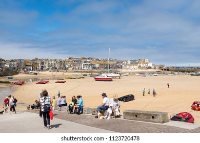 ST IVES, ENGLAND - JUNE 18: Tourists around the harbour in St Ives on a hot Summer day. In St Ives, Cornwall, England. On 18th June 2018.