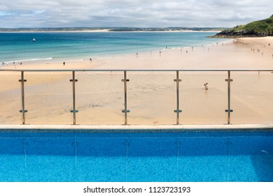 ST IVES, ENGLAND - JUNE 18: Vibrant blue hotel swimming pool at the edge of Porthminster Beach, St Ives, on a hot, Summer day. In St Ives, Cornwall, England. On 18th June 2018.