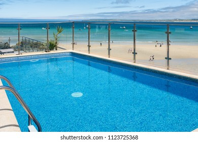 ST IVES, ENGLAND - JUNE 18: A vibrant blue hotel swimming pool at the edge of Porthminster Beach. In St Ives, Cornwall, England. On 18th June 2018.