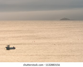ST IVES, ENGLAND - JUNE 19: A solitary fishing boat with Godrevy Lighthouse in the background, off the coast of St Ives. In St Ives, Cornwall, England. On 19th June 2018.