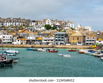 ST IVES, ENGLAND - JUNE 19: Lots of tourists visiting beautiful St Ives fishing harbour on a hot, sunny summer day. In St Ives, Cornwall, England. On 19th June 2018.