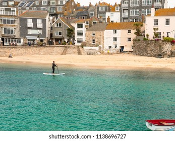 ST IVES, ENGLAND - JUNE 19: A man paddle boarding within St Ives harbour in Cornwall, UK. In St Ives, Cornwall, England. On 19th June 2018.