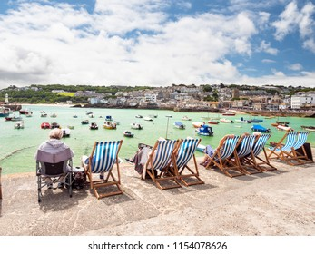 ST IVES, ENGLAND - JUNE 19: Elderly holiday makers, sitting in a row of deckchairs, enjoying the Summer sun in St Ives, Cornwall. In St Ives, England. On 19th June 2018.