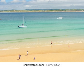 ST IVES, ENGLAND - JUNE 19: Families enjoying paddling in the sea at Porthminster Beach, in St Ives, on a hot Summer day. In St Ives, Cornwall, England. On 19th June 2018.