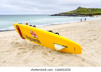 ST IVES, ENGLAND - JUNE 20: RNLI Lifeguards yellow surfboard on Porthmeor beach. In St Ives, Cornwall, England. On 20th June 2018.