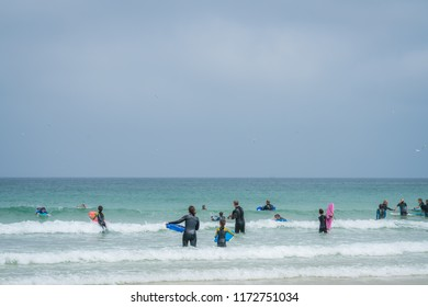 St. Ives, England -  May 2018 : Group of surfing adepts practising surfing with instructors in the sea, Cornwall, UK