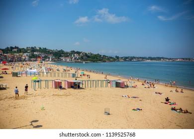 ST. JEAN DE LUZ, FRANCE - July 2018: People on the beach at St. Jean de Luz, Basque Country, France