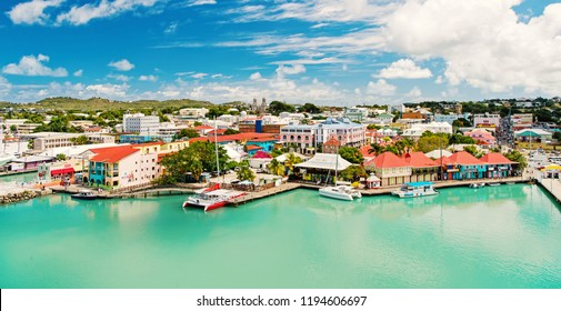 St. John, Antigua - March 05, 2016: bay with cute houses at harbor with yacht, boat, ship transport in sea, ocean water, blue cloudy sky sunny summer on natural background. traveling and vacation