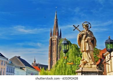 St. John of Nepomuk (John Nepomucene) statue on bridge with tower of Church of Our Lady (Onze-Lieve-Vrouwekerk), Brugge, Belgium