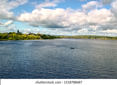 St John River with Fredericton New Brunswick Canada in the distance and a small fishing boat in the water