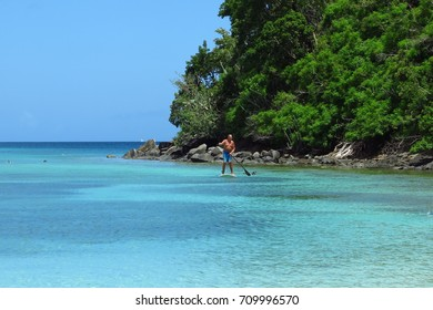 St. John, US Virgin Islands – July 17, 2017: A man navigates a paddle board past a snorkeler in the clear turquoise water at Maho Bay on St. John, USVI in the Caribbean.