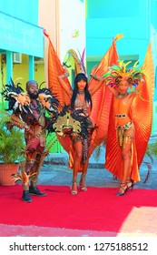 St Johns, Antigua, Caribbean - March 2nd 2018: A trio of people dressed in traditional, exotic, carnival costumes, entertaining tourists in the port of St Johns, Antigua.
